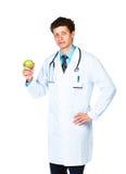 Retrato de um doutor masculino que guarda a maçã verde no branco imagem de stock