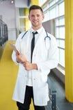 Retrato de um doutor masculino que guarda sua carta paciente no hospital moderno brilhante foto de stock royalty free
