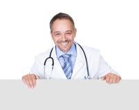 Retrato de um doutor que guarda o cartaz vazio imagens de stock