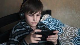 Retrato de um encontro feliz do menino do adolescente acordado com smartphone e fones de ouvido na cama que escuta a música em ca video estoque