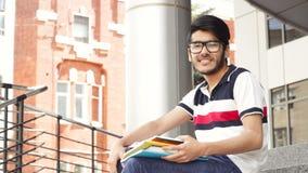 Retrato de um estudante asiático masculino de sorriso que senta-se em escadas e em livro de leitura filme