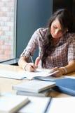 Retrato de um estudante bonito que escreve um ensaio Fotografia de Stock