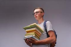 Retrato de um estudante do menino com uma trouxa e uma pilha de livros em suas mãos, confundida adolescente positivo engraçado da imagens de stock