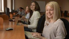 Retrato de um estudante fêmea alegre que trabalha no computador filme