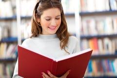 Estudante fêmea em uma biblioteca fotografia de stock