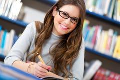 Estudante fêmea em uma biblioteca foto de stock