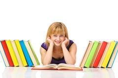 Retrato de um estudante novo que lê um livro que encontra-se em um assoalho Imagem de Stock