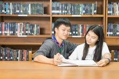 Retrato de um estudante novo sério que lê um livro em uma biblioteca fotografia de stock