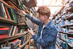 Retrato de um estudante que consulte livros das prateleiras da biblioteca pública Procure o livro na biblioteca fotos de stock