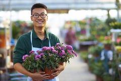 Retrato de um florista masculino novo feliz na loja Fotografia de Stock Royalty Free