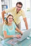 Retrato de um fones de ouvido vestindo da mulher e de seu colega Fotografia de Stock