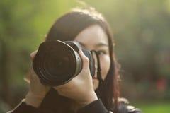 Retrato de um fotógrafo da natureza que cobre sua tela da câmera com a cara em uma floresta do parque da mola imagem de stock