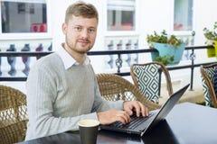 Retrato de um freelancer novo do moderno que trabalha em seu portátil durante comer o café da manhã em um café Imagem de Stock