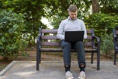 Retrato de um freelancer novo do moderno que trabalha em seu portátil que senta-se em um banco em um parque Fotografia de Stock Royalty Free