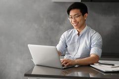 Retrato de um funcionamento asiático novo de sorriso do homem imagens de stock royalty free