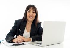 Retrato de um funcionamento feliz e seguro bonito novo da mulher de negócio no computador no escritório imagem de stock royalty free