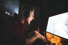 Retrato de um gamer mau nos fones de ouvido que jogam jogos de vídeo em um computador foto de stock royalty free