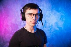 Retrato de um gamer novo alegre nos fones de ouvido Conceito dos jogos de computador foto de stock