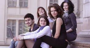 Retrato de um grupo de estudantes que sentam-se na frente da universidade Imagem de Stock Royalty Free
