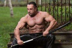 Retrato de um guerreiro antigo muscular com espada Fotografia de Stock