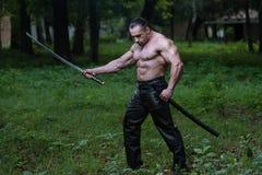 Retrato de um guerreiro antigo muscular com espada Foto de Stock