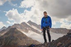 Retrato de um guia profissional de um alpinista em um tampão e em óculos de sol com um machado de gelo em sua mão contra imagens de stock