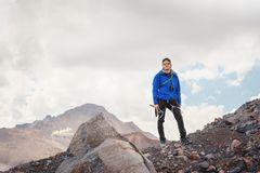 Retrato de um guia profissional de um alpinista em um tampão e em óculos de sol com um machado de gelo em sua mão contra fotografia de stock royalty free