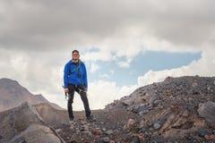 Retrato de um guia profissional do smiley de um alpinista em um tampão e em óculos de sol com um machado de gelo em sua mão contr fotografia de stock
