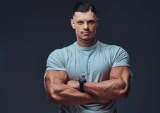 Retrato de um halterofilista considerável muscular no sportswear, estando com braços cruzados em um estúdio imagem de stock