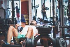 Retrato de um halterofilista masculino considerável que faz a imprensa de banco no gym da aptidão imagens de stock royalty free