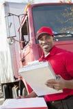 Retrato de um homem afro-americano feliz que guardara a prancheta com o caminhão de entrega no fundo imagem de stock royalty free
