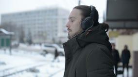 Retrato de um homem de cabelos compridos novo com uma barba nos fones de ouvido que estão em uma parada do bonde no inverno e que video estoque