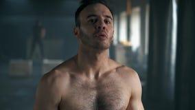 Retrato de um homem cansado muscular que olha a câmera com falta de ar após o treinamento duro movimento 4k lento filme