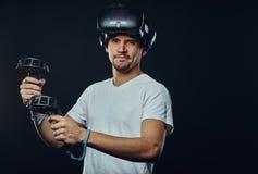 Retrato de um homem com a cerda vestida na camisa branca que veste os vidros da realidade virtual e os manches das posses, olhand imagem de stock royalty free