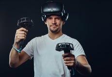 Retrato de um homem com a cerda vestida na camisa branca que veste os vidros da realidade virtual e os manches das posses, olhand imagem de stock