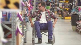 Retrato de um homem com vestir da inabilidade de uma cadeira de rodas na alameda vídeos de arquivo