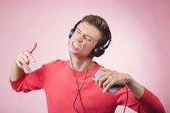 Retrato de um homem considerável novo com fones de ouvido que sorri e que escuta uma música com um smartphone fotografia de stock royalty free