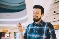 Retrato de um homem considerável novo com Mp3 e de fones de ouvido no fundo urbano imagem de stock