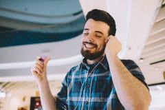 Retrato de um homem considerável novo com Mp3 e de fones de ouvido no fundo urbano fotos de stock