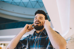 Retrato de um homem considerável novo com Mp3 e de fones de ouvido no urba imagem de stock