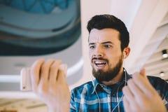 Retrato de um homem considerável novo com telefone e fones de ouvido no ur fotografia de stock royalty free