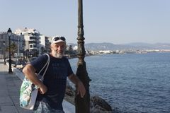 Retrato de um homem da idade madura em um poste de luz no wa de Loutraki Foto de Stock