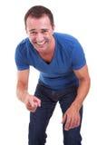 Retrato de um homem da médio-idade que aponta e que ri imagem de stock