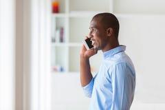 Retrato de um homem de negócio afro-americano novo que usa um móbil Imagem de Stock Royalty Free