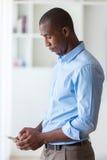 Retrato de um homem de negócio afro-americano novo que usa um móbil Imagens de Stock
