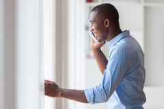 Retrato de um homem de negócio afro-americano novo que usa um móbil Imagens de Stock Royalty Free