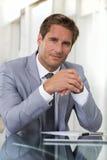 Retrato de um homem de negócios bem sucedido que senta-se em sua mesa, lookin Fotos de Stock Royalty Free