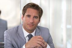 Retrato de um homem de negócios bem sucedido que senta-se em sua mesa, lookin Fotografia de Stock Royalty Free