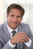 Retrato de um homem de negócios bem sucedido que senta-se em sua mesa, lookin Imagem de Stock
