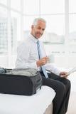 Retrato de um homem de negócios com o jornal da leitura do copo de café pela bagagem Imagens de Stock Royalty Free